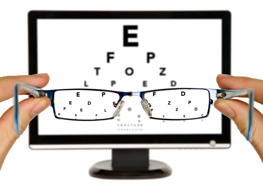 Man is viewing to eye examination chart on display through eyeglasses